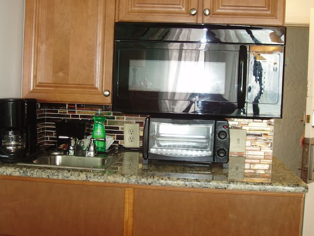 stocked kitchenette with silverware, glassware, microwave, toaster oven, coffee pot, snacks provided, mini fridge.