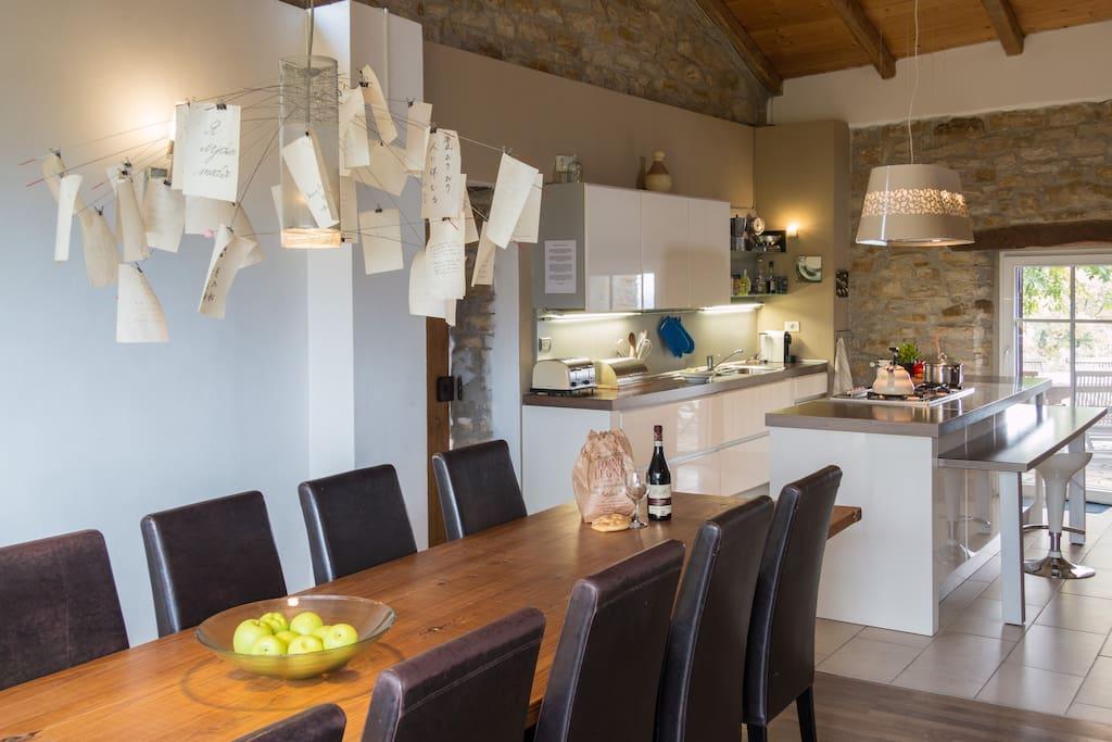 Blick vom langen Esstisch Richtung Küche mit Kochinsel