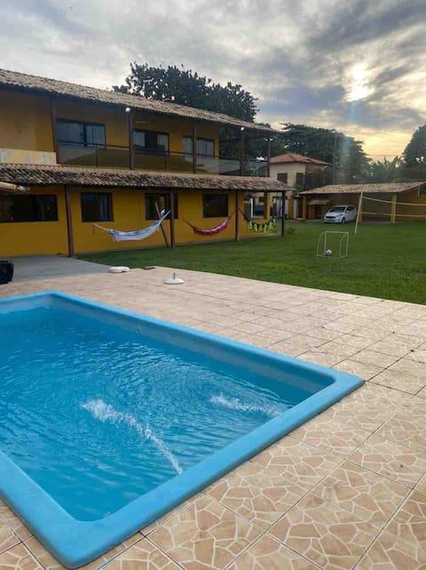 Casa amarela com piscina e vista para o mar.