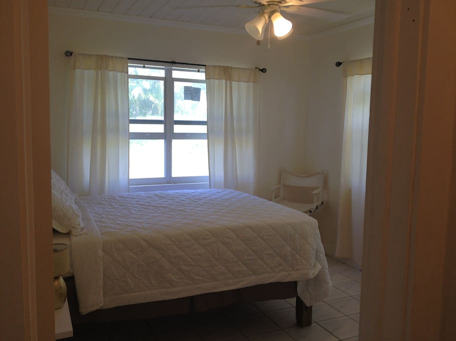Cozy Bedroom 1 with a Queen bed and large windows.