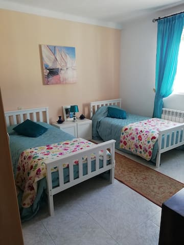 Twin bed room with views of patio/hills/mountains.. rear of house