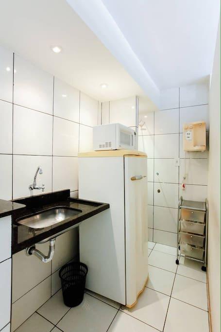 Cozinha: pia, geladeira, filtro, gavetas e utensílios básicos para as refeições. Não temos fogão forno, nem o microondas da imagem.