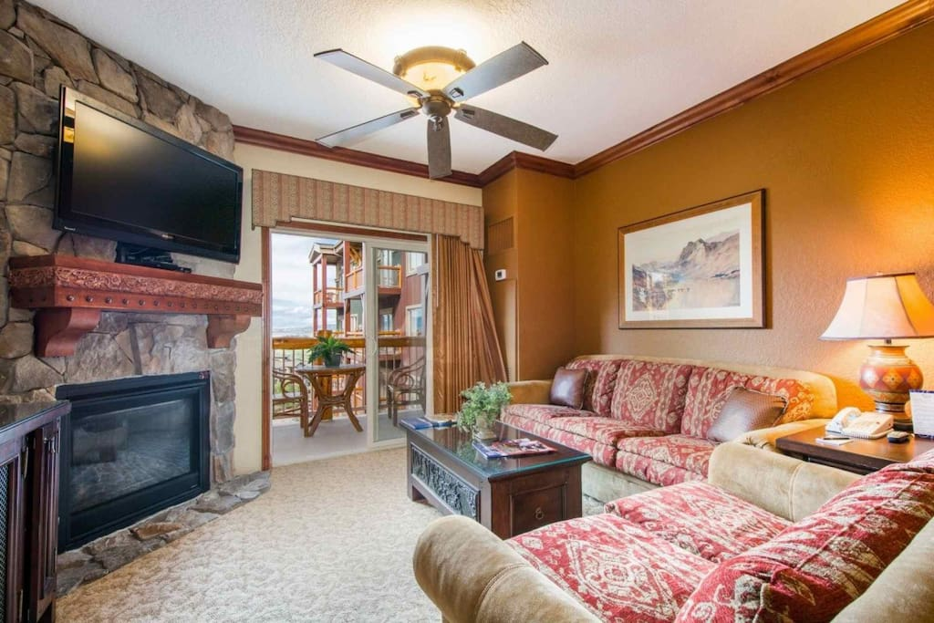 """The living room is equipped with a plush couch, love seat, 50"""" HDTV, enhanced cable, DVD player, Wi-Fi and beautiful stone fireplace."""