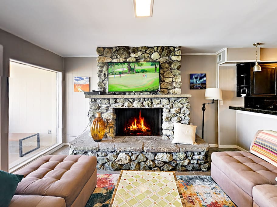 "A 50"" flat screen TV hangs over the stone fireplace in the living room."