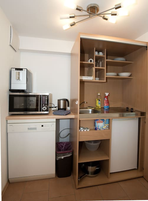Eine komplette kleine Küche mit Geschirr und allem, was es braucht.   Immer frischen Kaffee macht unser Kaffeevollautomat. Natürlich kümmern wir uns um die Bohnen.  Unsere Spülmaschine erledigt den Abwasch für dich.  Kochmuffel lassen die übrige Küche im Schrank verschwinden.