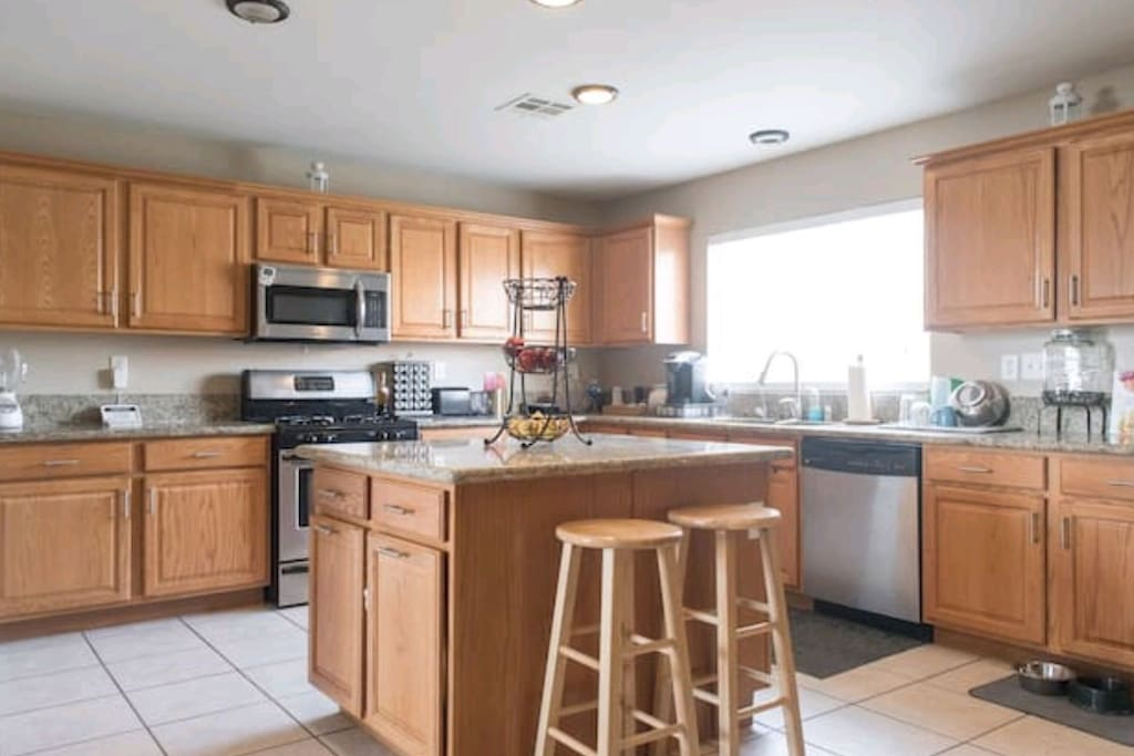 Large granite countertop kitchen with natural light and lots of space to cook.