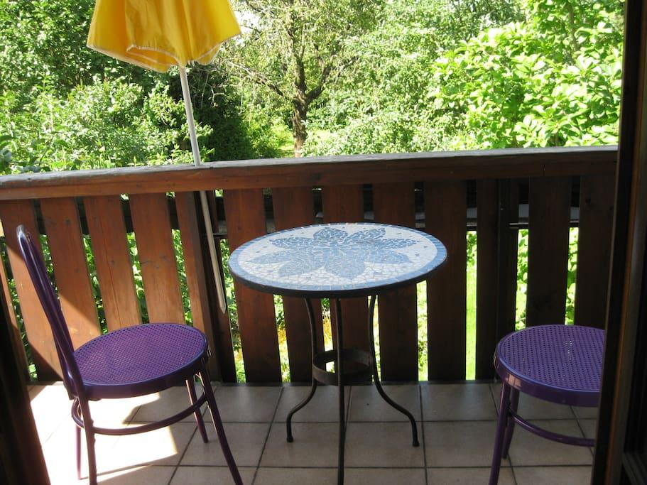 der Balkon zum Garten mit Tisch und 2 Stühlen