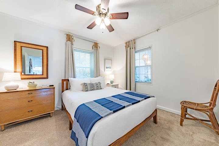 The Lake View Bedroom has a queen size memory foam bed, plush hotel grade bed linens, a dresser, bedside table, lamps, charging stations, and a large closet.