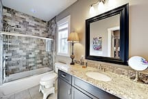 The guest bathroom is equipped with a tub/shower combination and a granite vanity.