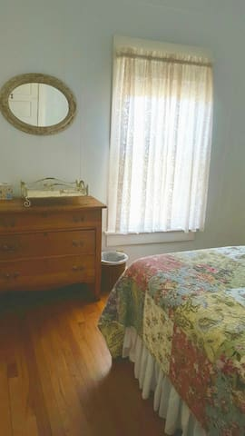 Main floor bedroom with the king sized bed and antique mirror and dresser.