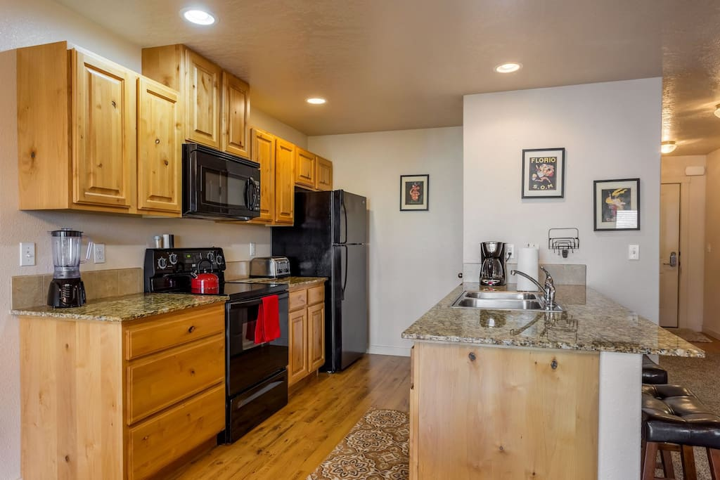 Fully stocked kitchen with granite counters and upgraded appliances