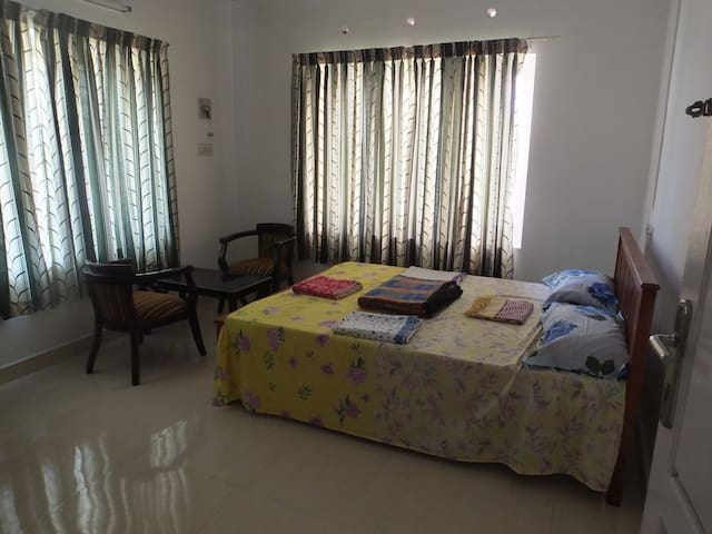 Bed room with AC, tea poy, chairs, writing table with chair, electric kettle and Almirah. Bath attached