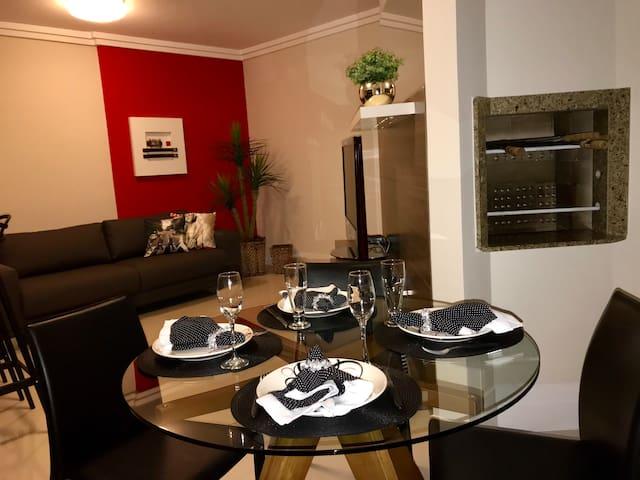 Sala de estar com TV, mesa com quatro cadeiras e churrasqueira, integrados.