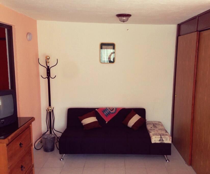 Es una habitación cómoda  cuenta con un sofá y un perchero