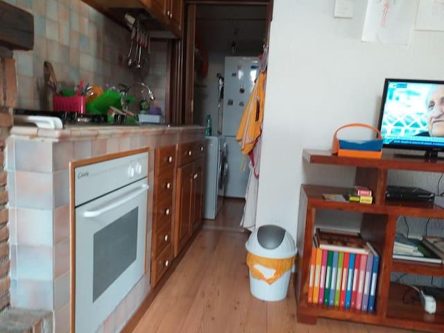Cucina in muratura e stanza con frigorifero e lavasciugatrice