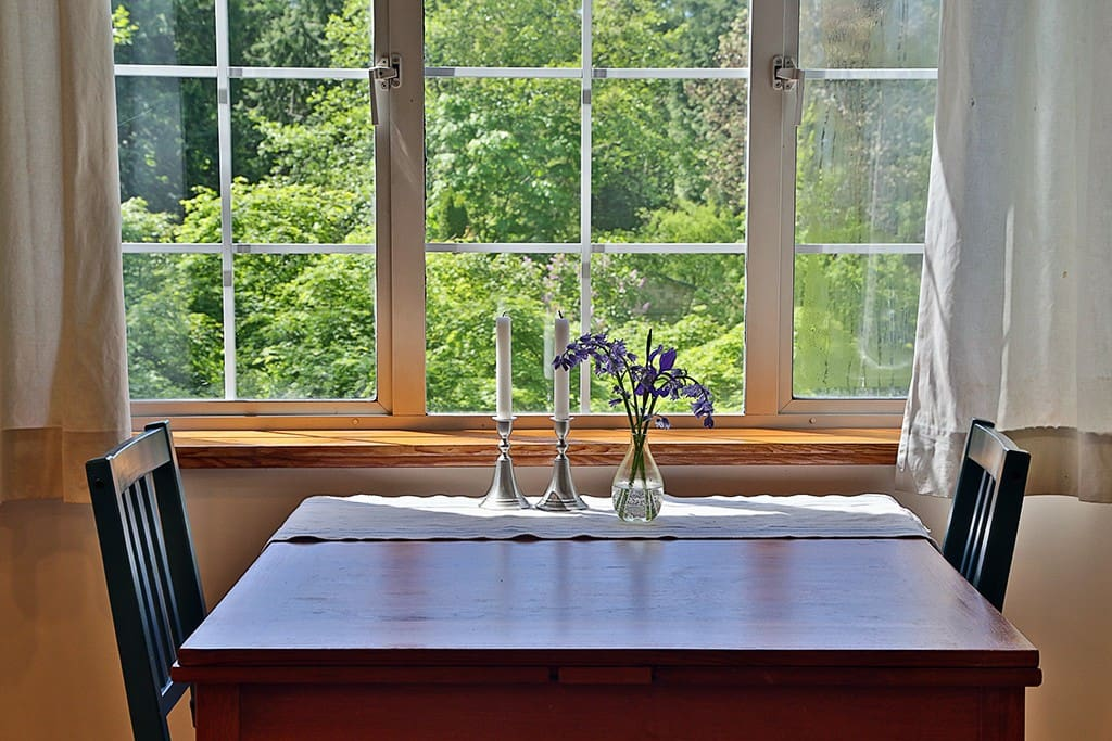 The table can seat six, through the window, looking down beyond a canopy of maple trees, there is a large yard. In the distance, a partial view of the Lapis Lane Cabin can be seen. The Cabin can be rented along with the Guesthouse for larger gatherings.
