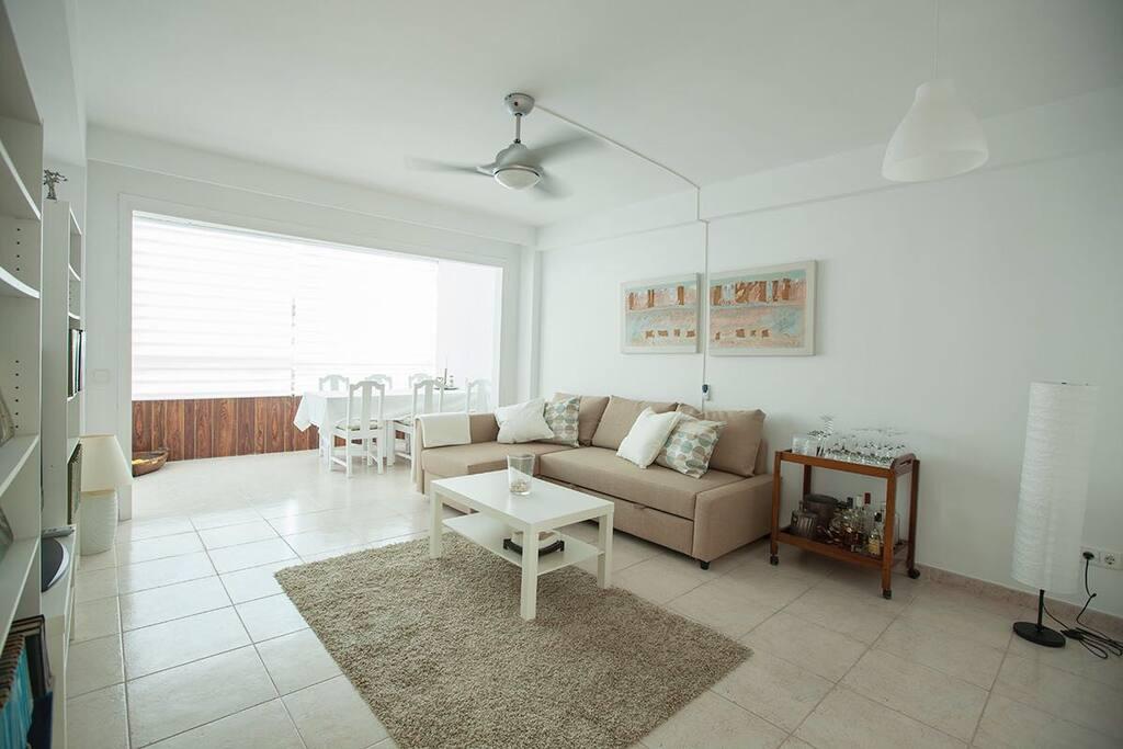 Amplio salón comedor con vistas despejadas, cómodo sofá con chaislongue y cama.