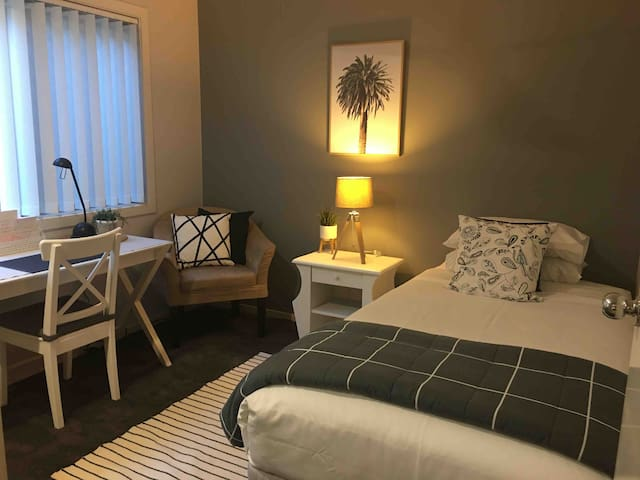 2nd bedroom has just been renovated with brand new carpet, luxury bedding with topper, quality sheets.  Bedroom is set up with one King Single bed, lovely quiet workspace with desk.  Can be a twin room with another bed added or a nursery for your bub