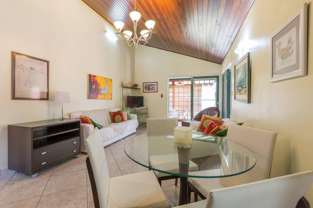Sala de estar, com mesa de jantar, TV a cabo e, ao fundo, jardim de inverno.