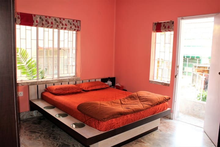 Red Room (Bedroom 2) in Natural Light with Attached Balcony