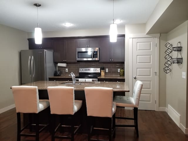 Kitchen pantry, large island, and stainless steel appliances including fridge, microwave, oven and dishwasher