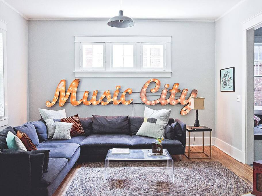 """Living Room – You'll feel like a star with the bright """"Music City"""" sign shining behind you in this decidedly artsy rental"""