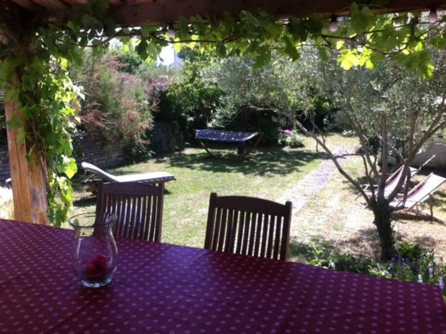 Préau couvert avec table pour 10 personnes donnant sur le jardin