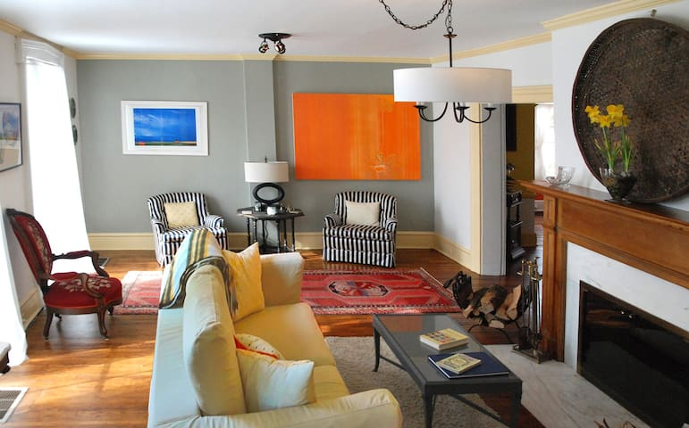 The living room features contemporary art, a wood burning fireplace with glass doors.