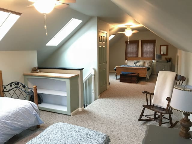 Upstairs bedroom with double bed, twin bed, and twin trundle bed features closet, shelves, and 2 dressers