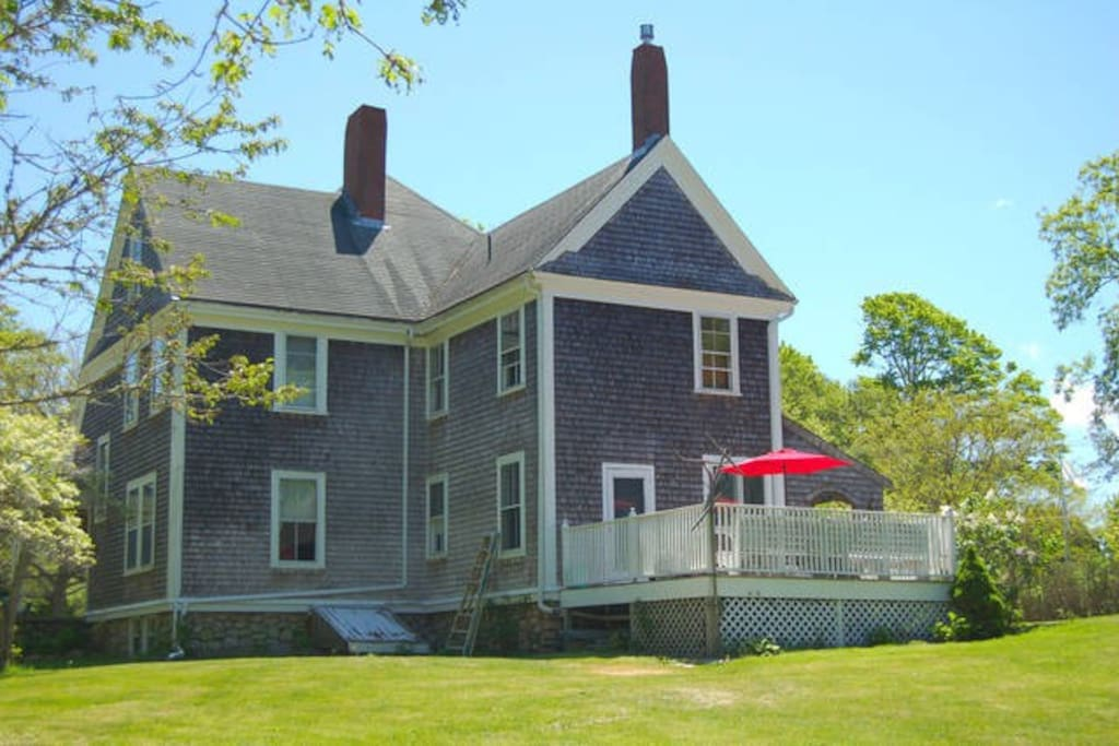 Back of house with large deck with table and chairs, grill and overlooking large private yard.