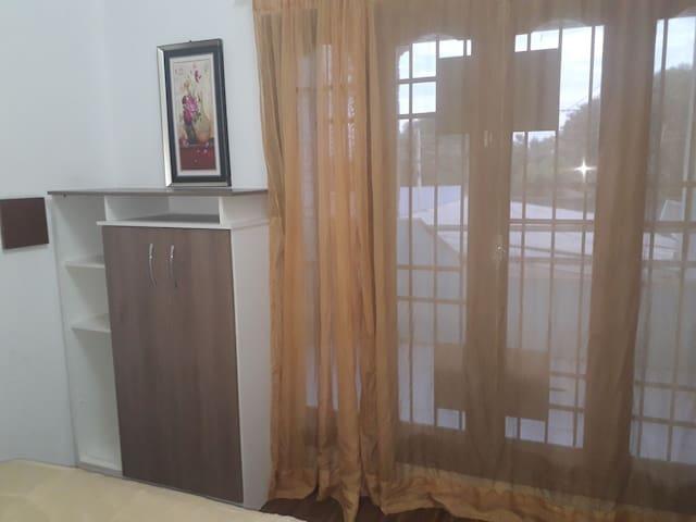 segundo dormitorio con acceso a un pequeño balcon