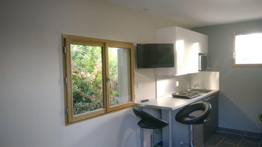 Espace cuisine avec table bar et TV