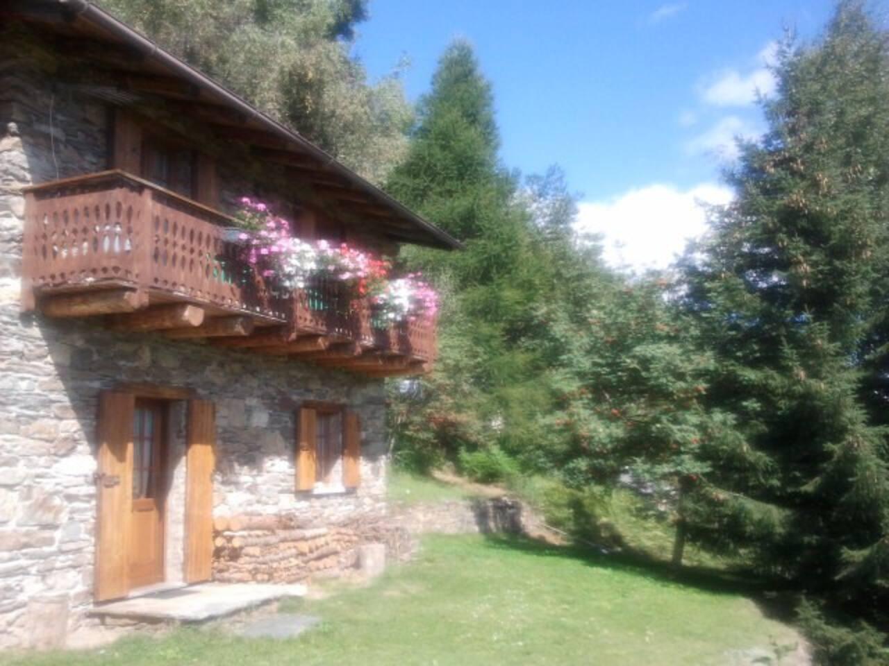 Baita col suo balcone fiorito in piena estate, davanti casa un bel spiazzo  molto riservato  e panoramico con barbecue