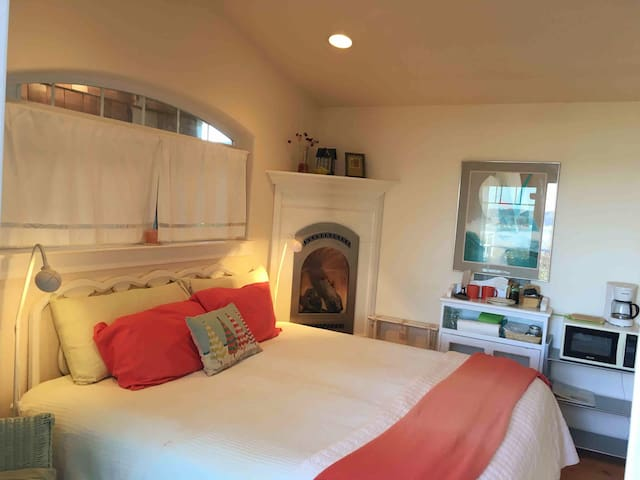 """The """"Annex,"""" master bedroom '2' with view to the water  king bed ( can be made into twins) en suite bathroom, safety bars, deck, fireplace, microwave, coffee pot, TV and small fridge."""