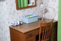 Writing desk, mirror, and toiletries.