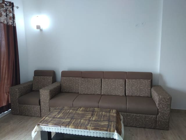 Breezy Living room fully furnished with comfortable sofa and 2 fans