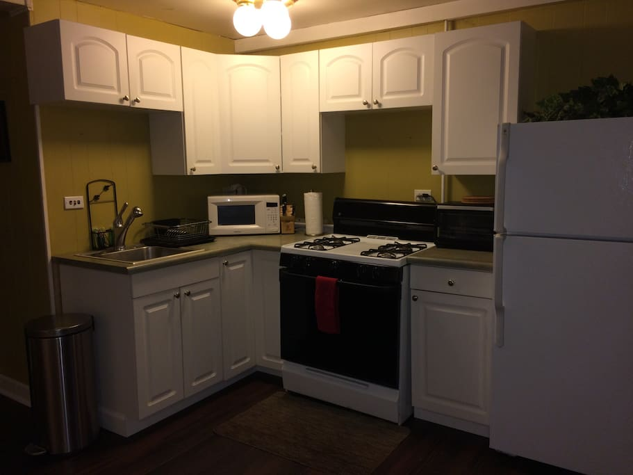 Full kitchen furnished with dinnerware, stovetop, microwave, toaster oven, fridge, and more.