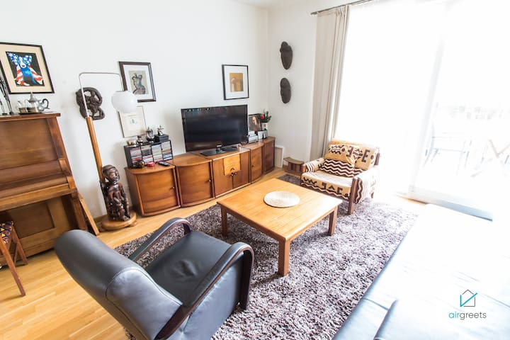 The living room offers a couch, two armchairs and a modern TV.