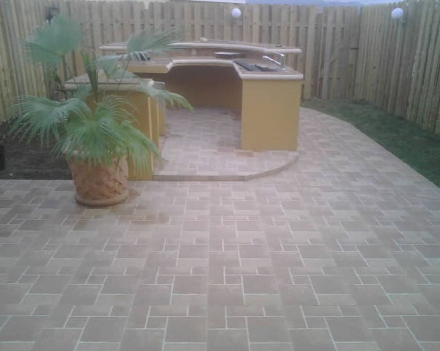 Backyard out door kitchen area with surrounding lights for entertainment