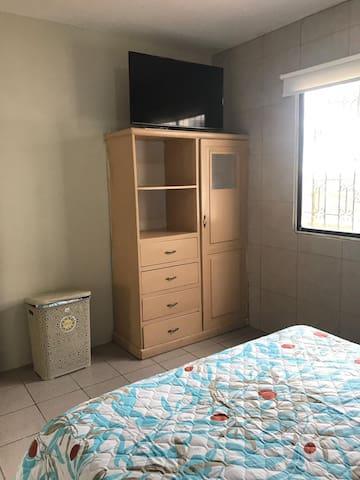 """Tacho, cama de 2plz y 1/2, closet de madera, veladores de madera con lamparas decorativas a cada lado de la cama, un reloj decorativo y smart tv de 49"""""""