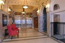 Historic lobby featuring original marble, elevator doors, light fixtures, flooring and more.
