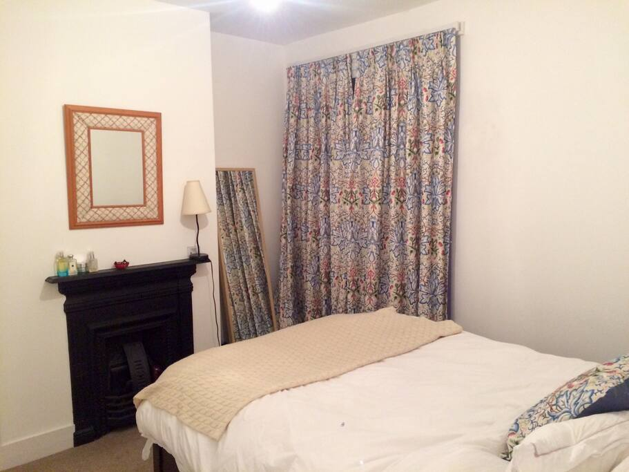 Bedroom features William Morris patterned curtains, tying in with the nearby William Morris museum.