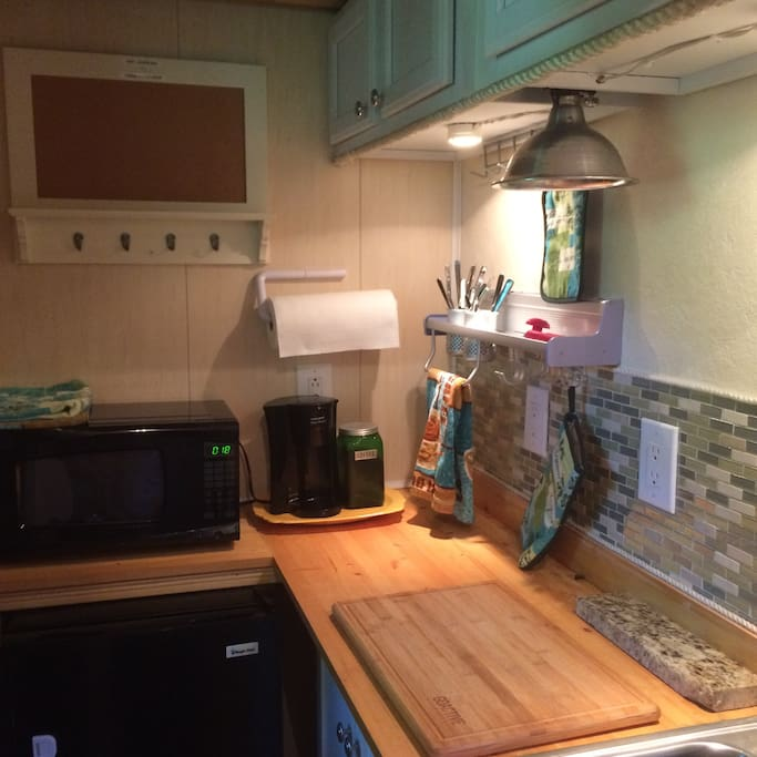 Kitchen area includes microwave fridge and coffee maker.
