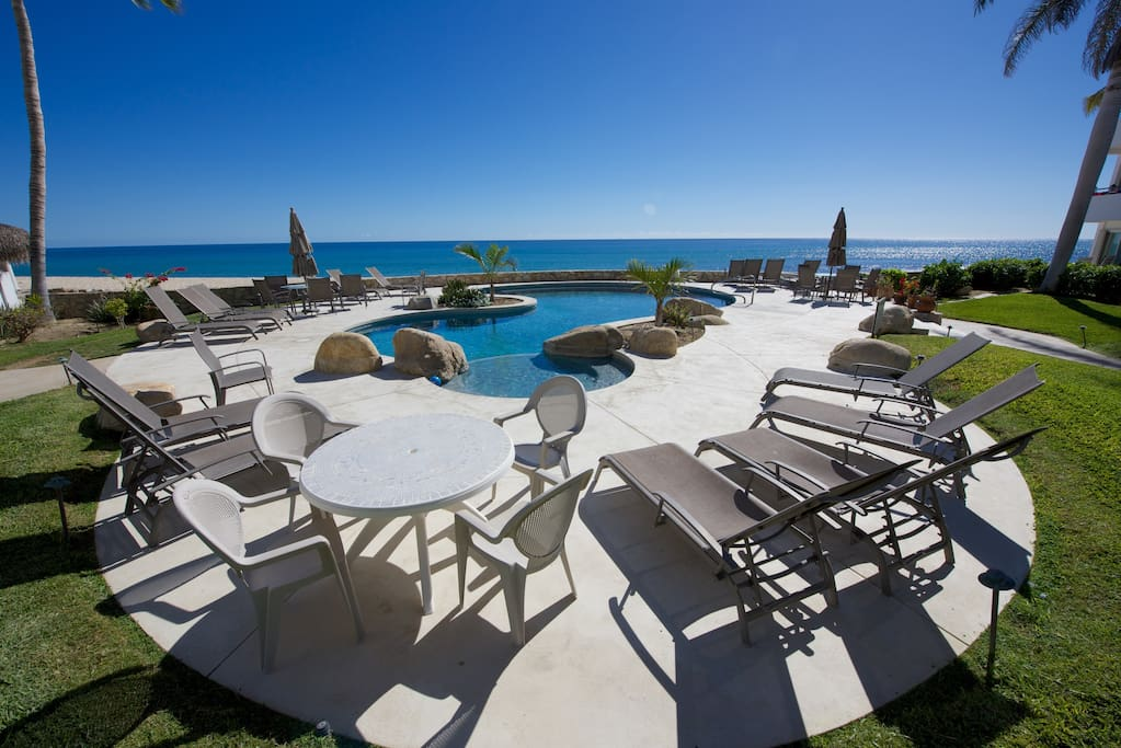 Lounge furniture around the pool and jacuzzi facing the beach