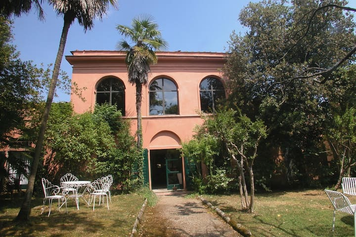 Home with large windows and original shutters on estate with pool and garden.