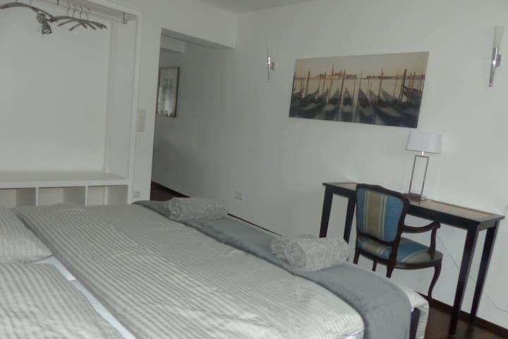 Schlafzimmer unterer Wohnungsbereich mit grossem Doppelbett offener Zugang zum Wohnzimmer, Bad auf gleicher Ebene