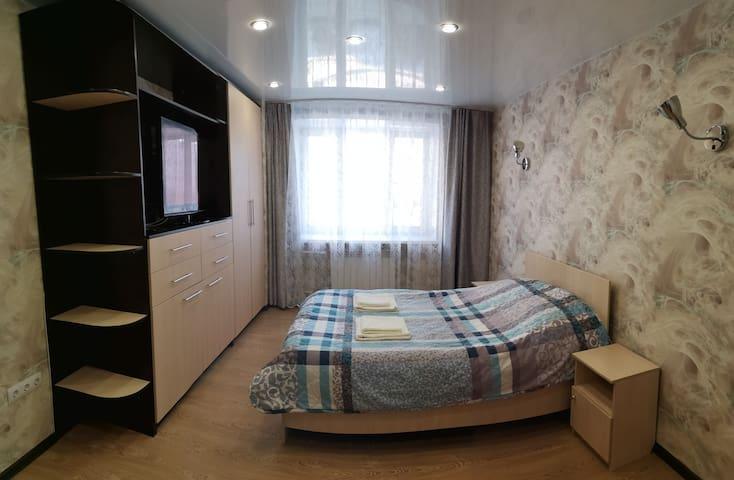 Просторная спальня с большим телевизором.