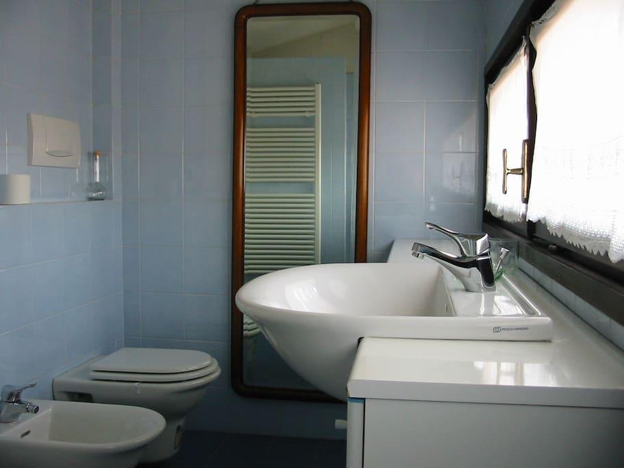 bagno con doccia e vista sui vecchi tetti della città
