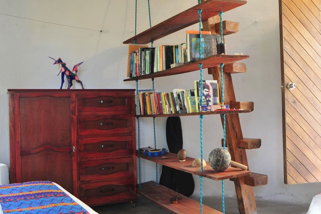 Borrow a book from the hanging bookshelf. The stairs are made out of a single beam of coconut wood. Easy to climb by most but might prove difficult for less mobile people.