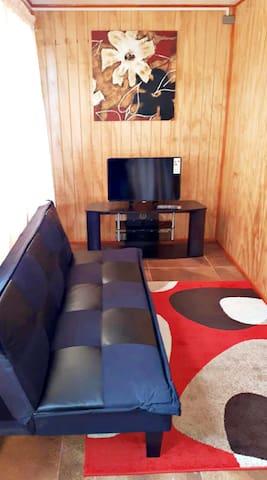 Living comedor, futón y Smart TV con cable.